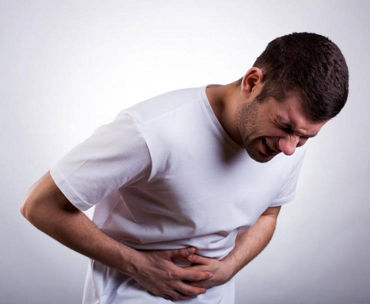 man-in-white-shirt-with-stomach-pain-against-gray-background